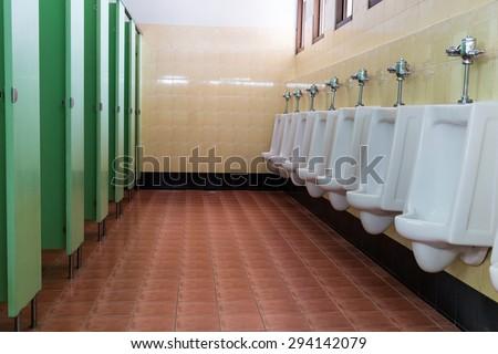 row white urinals in men's bathroom toilet - stock photo