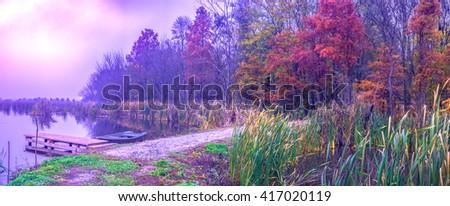 Rowboat anchored on the shore of lake in purple haze. Comana natural park, Comana village, Giurgiu county, Romania.  - stock photo