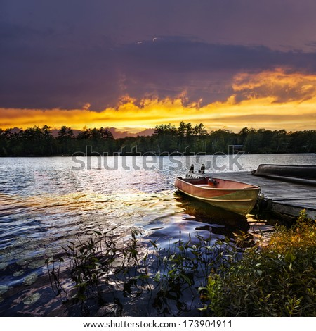 Rowboat tied to dock on beautiful lake with dramatic sunset - stock photo
