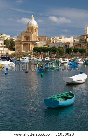Rowboats bob at anchor in the harbor before St Joseph's Church, Vittoriosa, Malta