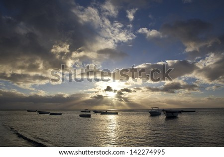 Rowboats in ocean on Mauritius island at sundown - stock photo