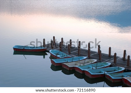 rowboats in pier at dawn - stock photo