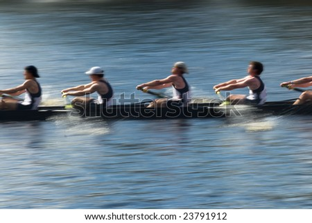 Rowers in a rowing boat pulling in harmony, motion blurred to accent speed - stock photo