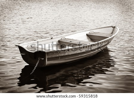 Rowing boat in black and white in calm water. - stock photo