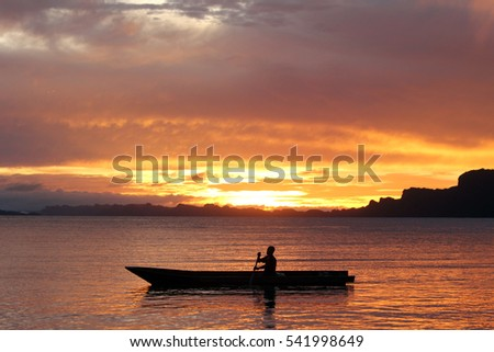 Rowing boat in the sunset in Raja Ampat Indonesia