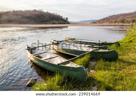 Rowing boat lying on the banks of a river lit by morning sun - stock photo
