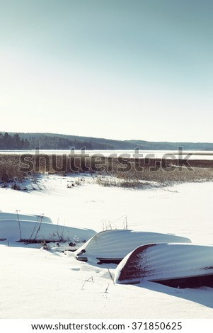 Rowing boats are parked on the beach during spring time. Some snow is on the ground and boats. Sun is shining on a cold winter day in Finland. Image has a vintage effect applied. - stock photo