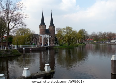 Rowing team in a coxed four rowing past a historic, fortified . Delft . Netherlands - stock photo