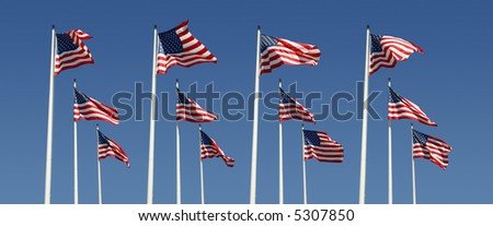 rows of american flags on a bright blue sky