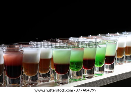 Rows of beautiful multicolored bright green red orange white alcohol tasty sweet delicious shots drinks in drinking glasses standing on bar on black background closeup studio, horizontal picture  - stock photo