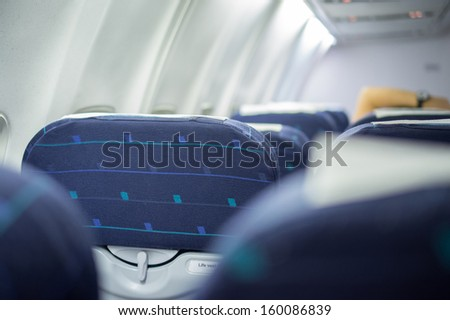 Rows of blue empty passengers seats in airplane - stock photo