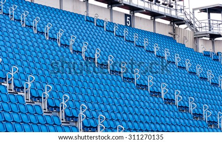rows of blue seats in a stadium - stock photo