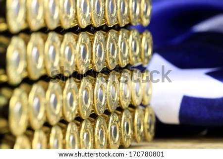 Rows of 45 caliber ammunition copper plated bullets with US flag in background - stock photo