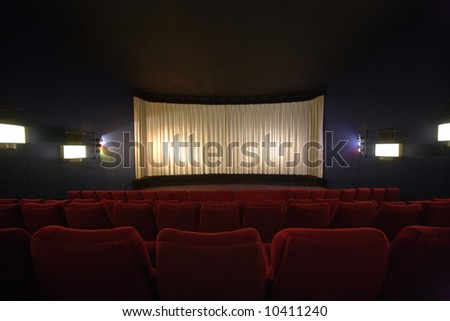 Rows of chairs in a cinema with the curtain drawn - stock photo