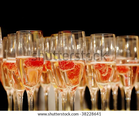 Rows of Champagne with Raspberry Garnish for New Year's Eve - stock photo