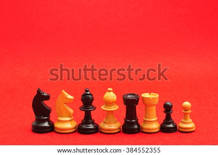 Rows of chess pieces displayed on a red background