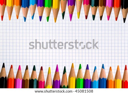 Rows of color pencils on a blank squared notebook sheet - stock photo