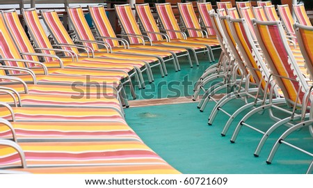 Rows of colorful chaise lounges on a green deck