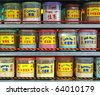 Rows of colorful container containing food extract flavoring powder on the shelf of a Chinese street stall. - stock photo