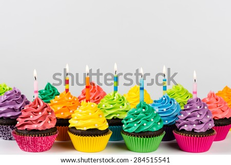 Rows of colorful cup cakes decorated with birthday candles and sprinkles. - stock photo