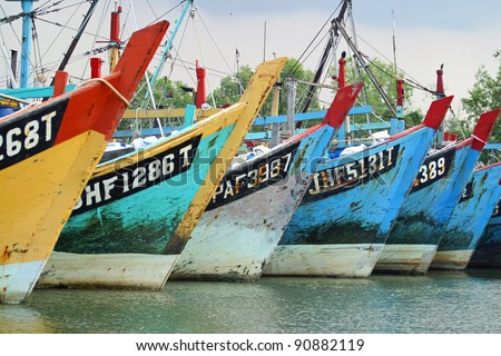 Rows of colorful fishing boat waiting to go out to the sea. - stock photo