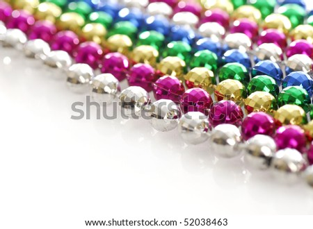 rows of colorful mardi gras beads strung out in a line with reflection on white background - stock photo