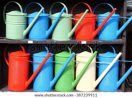 Rows of colorful watering cans - stock photo