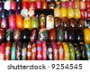 Rows of colorful wooden hand-painted bracelets - shallow DOF. - stock photo