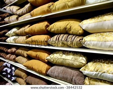 Rows of decorative pillows on shelves - stock photo