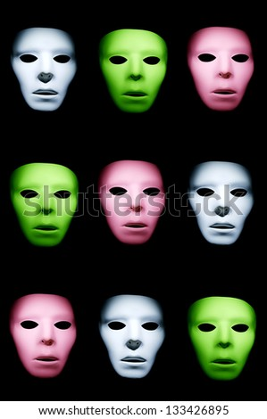 Rows of different color ghostly alien like faces against a black background. - stock photo