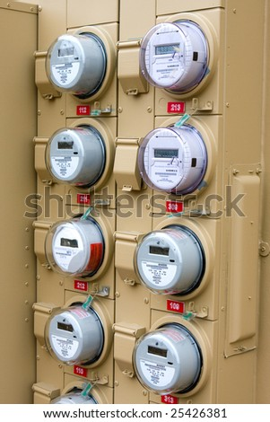 Rows of electric meters line the outside wall of a new apartment building. - stock photo