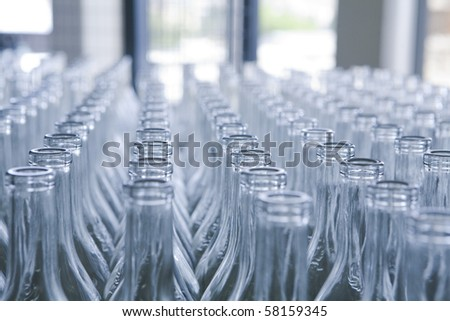 rows of empty bottles at bottling plant with swallow depth of field - stock photo