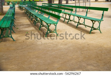Rows of empty green park benches on gravel