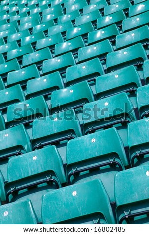 Rows of empty green plastic seats in a sports stadium. - stock photo
