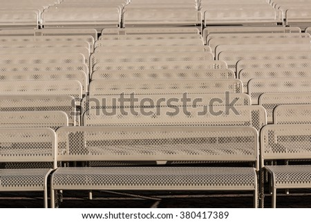 Rows of empty outdoor audience benches facing center - stock photo