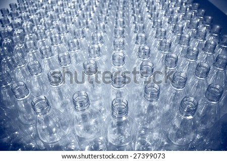 rows of empty plastic bottles at bottling plant - stock photo