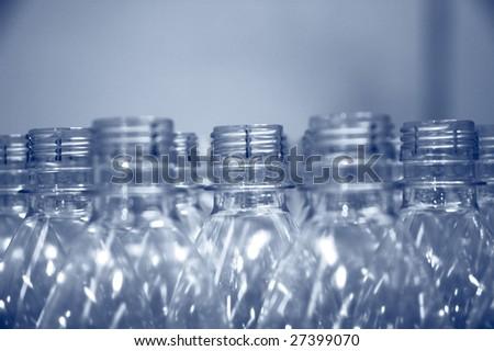 rows of empty plastic water bottle necks - stock photo