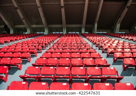 Rows of empty red plastic seats going upward on step with pathway in a stadium. Select focus - stock photo