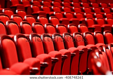 Rows of empty red velvet seats inside a theater - stock photo