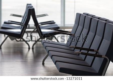 rows of empty seats in waiting room of modern airport