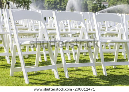 Rows of empty white folding chairs sitting on a lawn. - stock photo