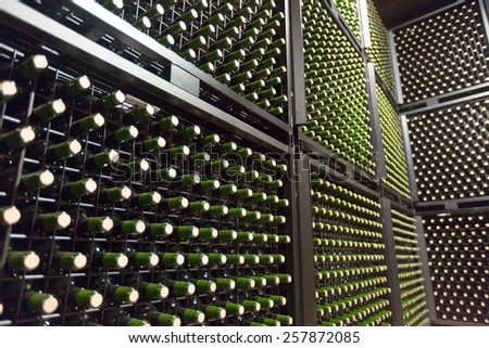 Rows of glass green bottles in winery - stock photo