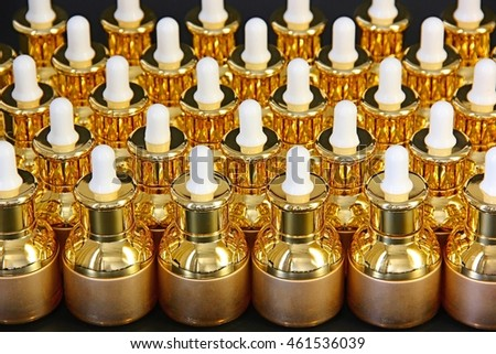 Rows of golden cosmetic bottles on black background.