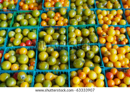 Rows of green, yellow, orange, and red cherry tomatoes at the farmers market - stock photo