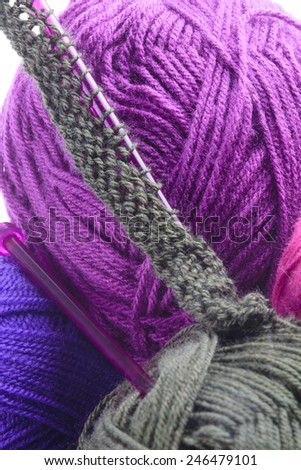 Rows of grey pearl stitches cast on a plastic knitting needle amongst balls of colorful purple, and grey wool showing the texture of the needlework and fibers of the wool - stock photo