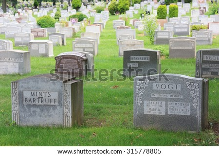 Rows of grey stone tombstones in cemetery in Queens. Two first row tombstones in focus, others progressively out of focus - July 2, 2015, New York City, NY, USA - stock photo