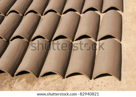 Rows of handmade clay roofing tiles drying in the sun - stock photo