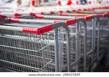 Rows of heavy shopping carts at the entrance of supermarket - stock photo