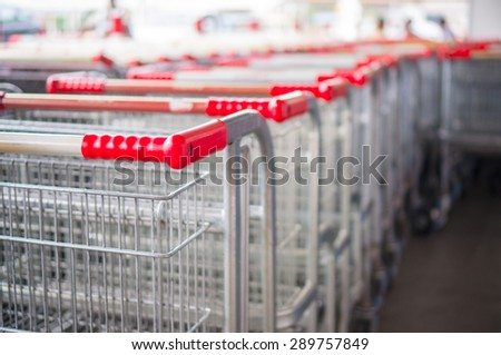 Rows of heavy shopping carts at the entrance of supermarket