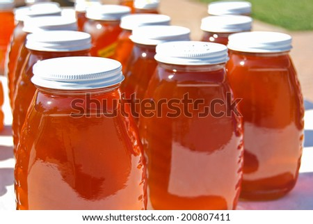 rows of honey in glass jars at the farmer's market